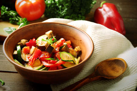 Tasty vegetarian ratatouille made of eggplants, squash, tomatoes in bowl on wooden table background