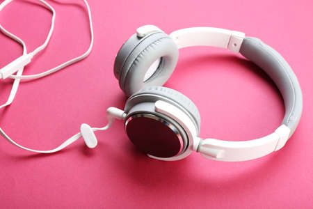White and grey headphones on pink background