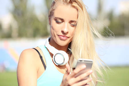 Young woman listening to music on the stadium Stock Photo