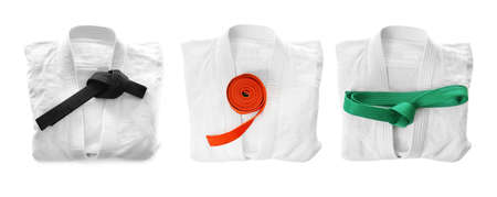 Set of karate uniforms with belts on white background