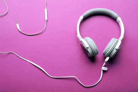 White and grey headphones on purple background