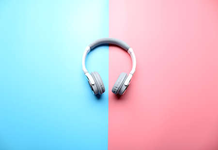 Wireless white and grey headphones on pink-blue background Stock Photo
