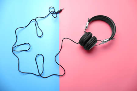 Black headphones on pink-blue background