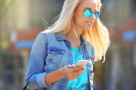 Young woman listening to music and walking along the street