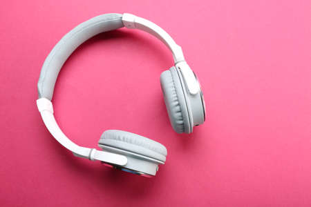 Wireless white and grey headphones on pink background
