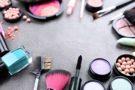 Decorative cosmetics laying out as a frame on grey background
