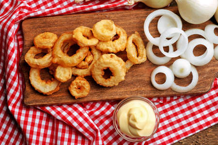 Chips rings with sauce and onion on cutting board Reklamní fotografie