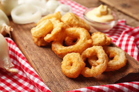 Chips rings with sauce and onion on cutting board Foto de archivo