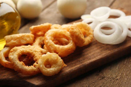 Chips rings with sauce and onion on cutting board Stock Photo