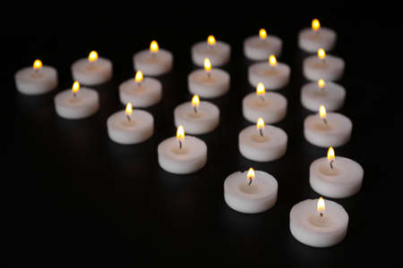 Alight candles in a row on black background Stock Photo