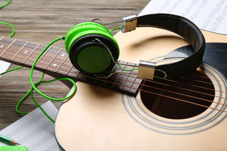 Classical guitar and headphones with notes on wooden background