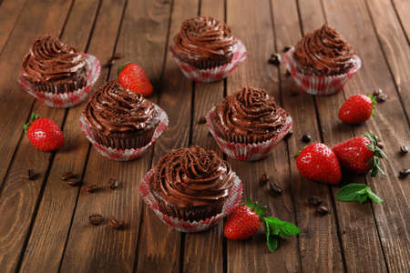 Chocolate cupcakes and strawberries on wooden background