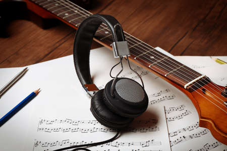 Electric guitar and headphones with music notes on wooden background, close-up Stock Photo
