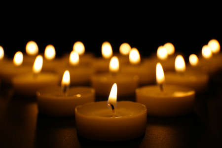 Alight candles in a row on black background Imagens