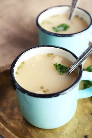 Mugs of soup on metal tray on a table Stock Photo