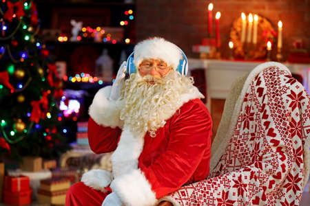 Santa Claus sitting with headphones sitting in comfortable rocking chair at home Stock Photo
