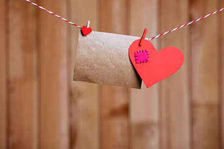 Paper hearts and empty sheet hanging on cord against wooden background