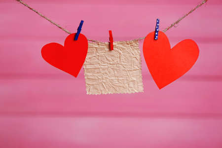 Paper hearts and empty sheet hanging on cord against pink wooden background