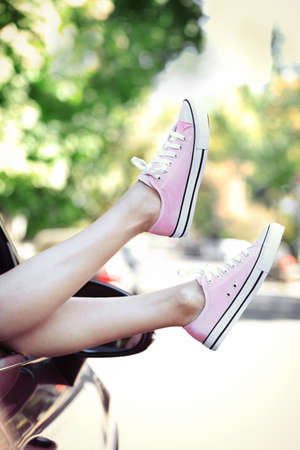 Womans legs out of the car window. Stock Photo