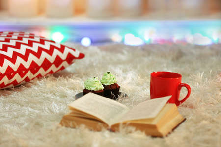 Composition with warm plaid, book, cup of hot drink on colorful lights background Stock Photo