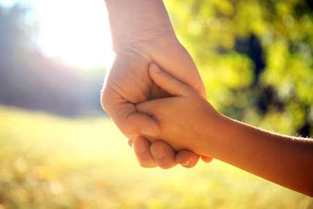 親は小さな子供の手を握る