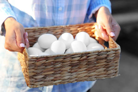 Eggs in basket in women hands close-up Stock Photo