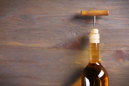 Corkscrew and wine bottle on wooden background