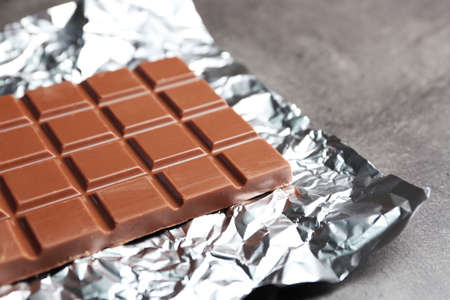 Chocolate bar in foil  on gray background Stock Photo