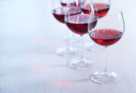 Glasses of red wine on table on bright background Stock Photo