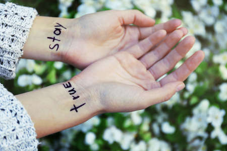 Hands of young woman with tattooed words on it, on white flowers background, close-up