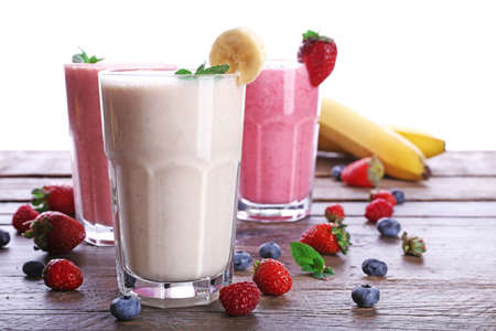 Glasses of fresh cold smoothie with fruit and berries, isolated on white