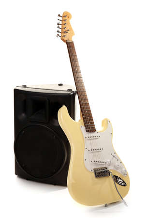 Electric guitar with musical equipment on light background