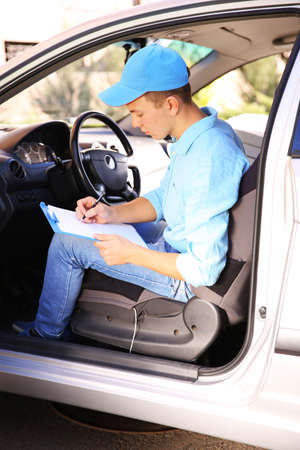 Pizza delivery boy with tablet in car, close-up Stock Photo