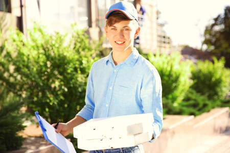 Pizza delivery boy holding boxes with pizza, outdoors Stock Photo