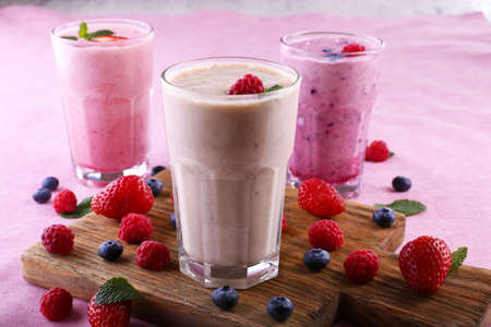 Milkshakes at cutting board with berries on light background Stock Photo