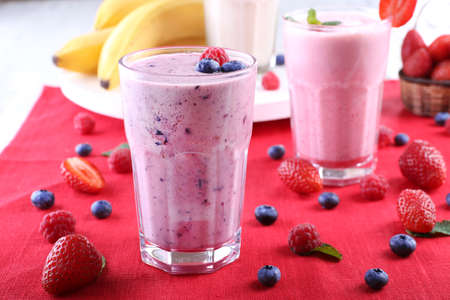 Milkshakes with berries at red textile on light background Stock Photo
