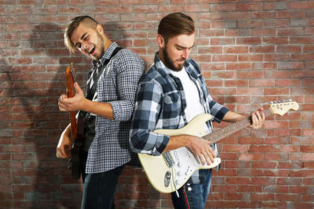 Young men playing guitars on brick wall background