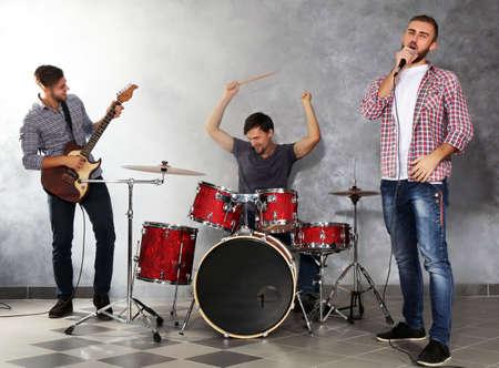 Músicos tocando instrumentos musicais e cantando músicas em um estúdio