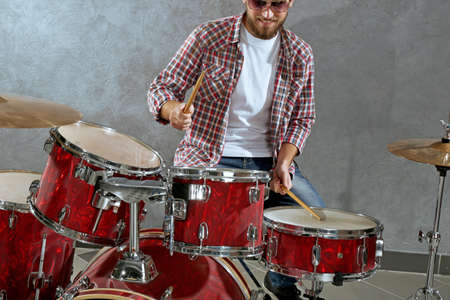 Musician playing the drums on grey wall background