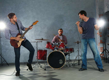 Musicians playing musical instruments and singing songs in a studio Stock Photo