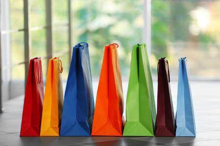 De kleurrijke document het winkelen zakken defocused achtergrond Stockfoto