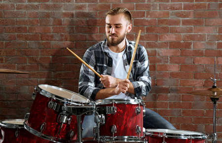 Musician playing the drums on brick wall background Foto de archivo