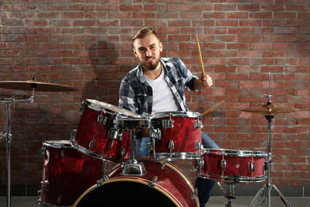 Musician playing the drums on brick wall background Stockfoto - 95091785