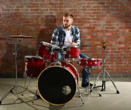 Musician playing the drums on brick wall background Stock Photo