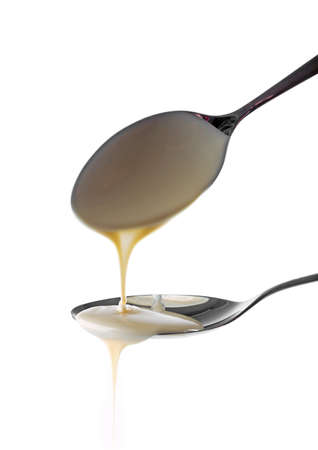 Condensed milk pouring from spoons, isolated on white Stock Photo