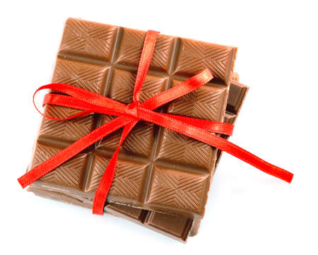 Milk chocolate bar with red bow on color wooden background Фото со стока