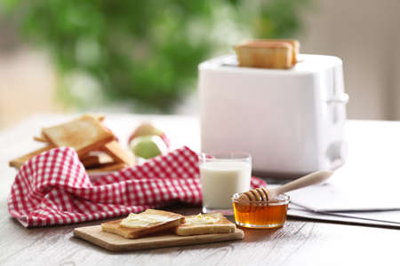 Served table for breakfast with toast, milk and jam, close-up Archivio Fotografico