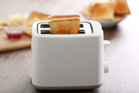 A couple of crusty toast in the toaster on the table, close-up