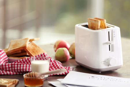 Served table for breakfast with toast, milk and honey, on blurred background Foto de archivo