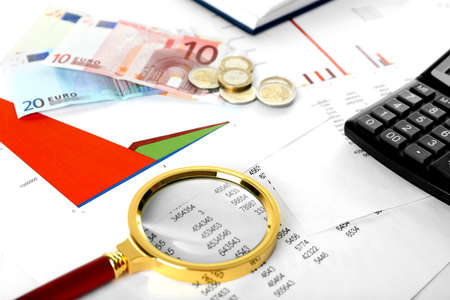 A magnifying glass on financial documents background, close-up Stock Photo